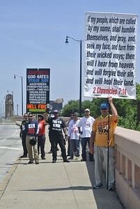 DAVID KNOX / GAZETTE A group of religious fundamentalists, called Bible Believers, use a bullhorn to taunt Stand Together Against Trump demonstrators as they prepared to march across the Lorain-Carnegie Bridge Thursday afternoon.
