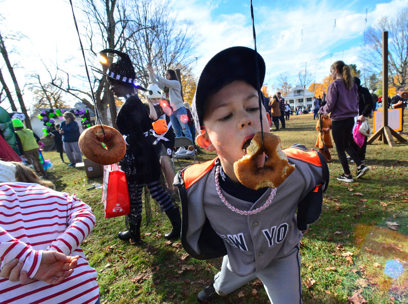KRISTOPHER RADDER — BRATTLEBORO REFORMER<br /> Anderson Kohler, 9, from Keene, N.H., tries to use no hands when eating a doughnut on a string during a trunk-o-treat event at the Chesterfield Elementary School, in Chesterfield, N.H., on Saturday, Oct. 26, 2019.