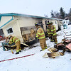 KRISTOPHER RADDER - BRATTLEBORO REFORMER<br /> Members of the Hinsdale Fire Department look under the mobile home where the fire started.