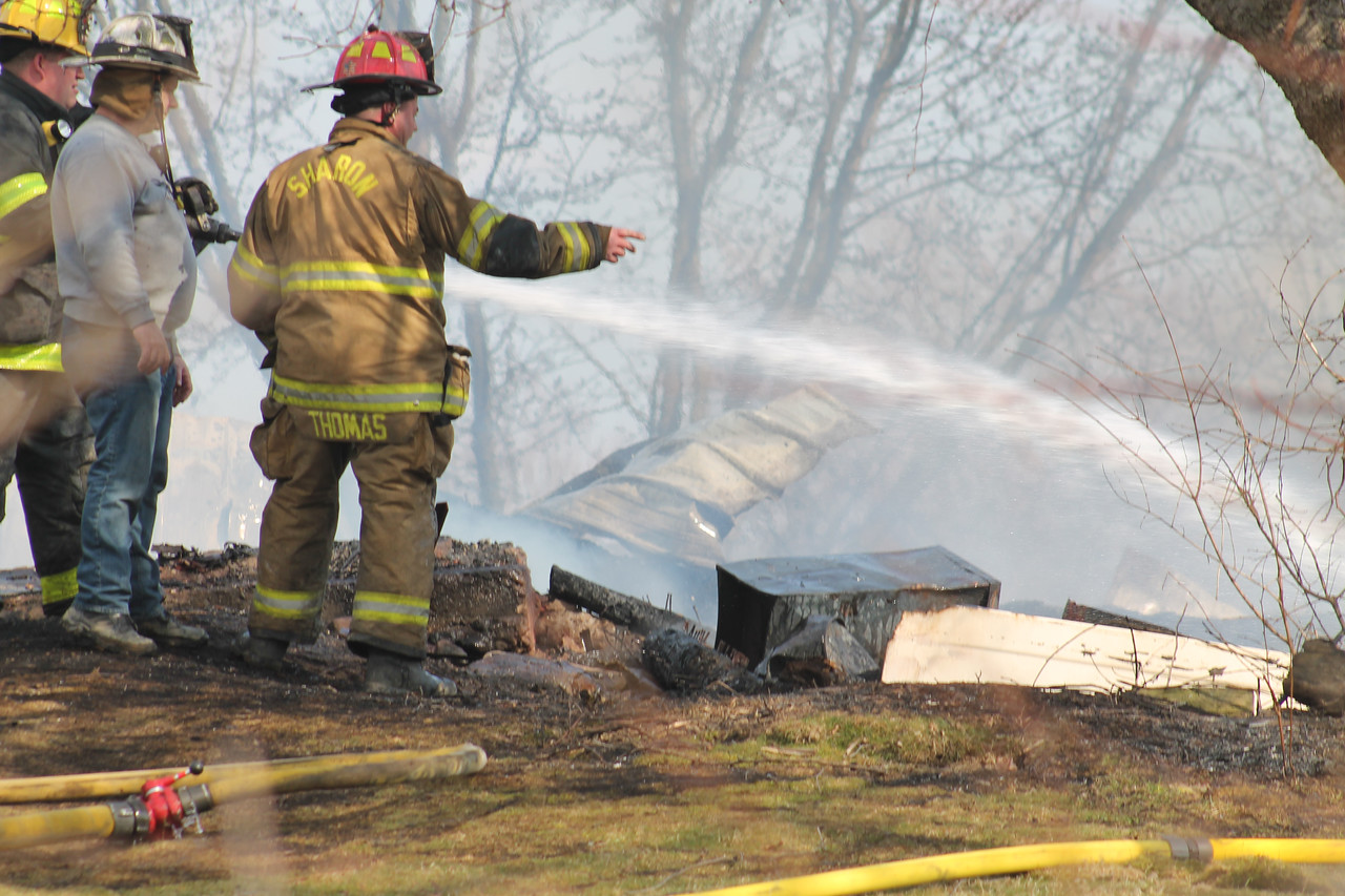 LAWRENCE PANTAGES / GAZETTE Sharon Township Fire Chief Rob Haas (second from left) watches as firefighters complete work Wednesday afternoon to stop a blaze that demolished a 40 by 60 foot barn at 972 Ridgewood Road.