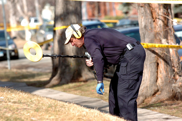 Investigators use metal detectors at  the scene of an overnight shooting on University Hill on Friday morning.<br /> Photo by Paul Aiken