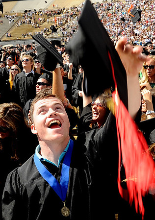 """Alex Schultz, a graduate of the School of Journalism, throws his cap in the air  at the end of the ceremony.<br /> A total of 5,897 degrees were conferred during the University of Colorado Spring 2011 Commencement on Friday.<br /> For more photos and a video of graduation, go to  <a href=""""http://www.dailycamera.com"""">http://www.dailycamera.com</a>.<br /> Cliff Grassmick/ May 6, 2011"""