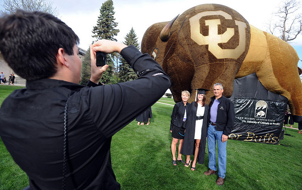 """Andy Librande of Loveland, photographs his family, Terry, Elizabeth and Mark in front of the Buffalo.<br /> A total of 5,897 degrees were conferred during the University of Colorado Spring 2011 Commencement on Friday.<br /> For more photos and a video of graduation, go to  <a href=""""http://www.dailycamera.com"""">http://www.dailycamera.com</a>.<br /> Cliff Grassmick/ May 6, 2011"""