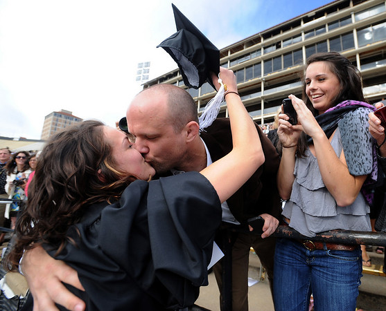 """Andrew Dudderar gives his graduate girlfriend, Brittney Gaillot, a kiss before the ceremony, as sister Kelesey Gaillot, looks on. <br /> A total of 5,897 degrees were conferred during the University of Colorado Spring 2011 Commencement on Friday at Folsom Field in Boulder, Colo.<br /> For more photos and a video of graduation, go to  <a href=""""http://www.dailycamera.com"""">http://www.dailycamera.com</a>.<br /> Cliff Grassmick/ May 6, 2011"""