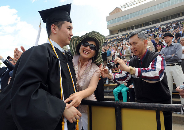 "Graduate Edwin Sun, left, gets hug from his mom, Teresa, as uncle William prepares the camera.<br /> A total of 5,897 degrees were conferred during the University of Colorado Spring 2011 Commencement on Friday.<br /> For more photos and a video of graduation, go to  <a href=""http://www.dailycamera.com"">http://www.dailycamera.com</a>.<br /> Cliff Grassmick/ May 6, 2011"