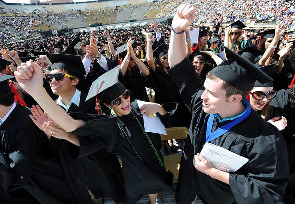 """Journalism grads, Michelle Davenport, left, and Alex Schultz, celebrate their graduation near the end of the ceremony.<br /> A total of 5,897 degrees were conferred during the University of Colorado Spring 2011 Commencement on Friday.<br /> For more photos and a video of graduation, go to  <a href=""""http://www.dailycamera.com"""">http://www.dailycamera.com</a>.<br /> Cliff Grassmick/ May 6, 2011"""