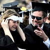 Josh Davies (right), graduate in Anthropology, laughs while Annika Johnson (left), graduate in International Affairs, tries on a pair of sunglasses she fashioned from her program during the commencement ceremony held in Folsom Field at the University of Colorado in Boulder, Colorado May 6, 2011.  CAMERA/Mark Leffingwell