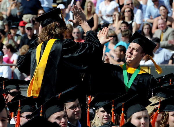 """Master's degree candidates, Ryan Del Gizzi, left, and Dan Ambrosio, celebrate with high fives during their announcement.<br /> A total of 5,897 degrees were conferred during the University of Colorado Spring 2011 Commencement on Friday.<br /> For more photos and a video of graduation, go to  <a href=""""http://www.dailycamera.com"""">http://www.dailycamera.com</a>.<br /> Cliff Grassmick/ May 6, 2011"""