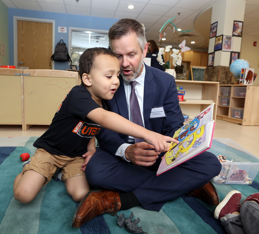 . Ribbon cutting and dedication of the Nancy L. and Richard K. Donahue UTEC Hub for Social Innovation. Isaiah Whitson, 4, of Lowell, who goes to the UTEC preschool, reads a book with Tom Weber, Early Education and Care Commissioner. (SUN/Julia Malakie)