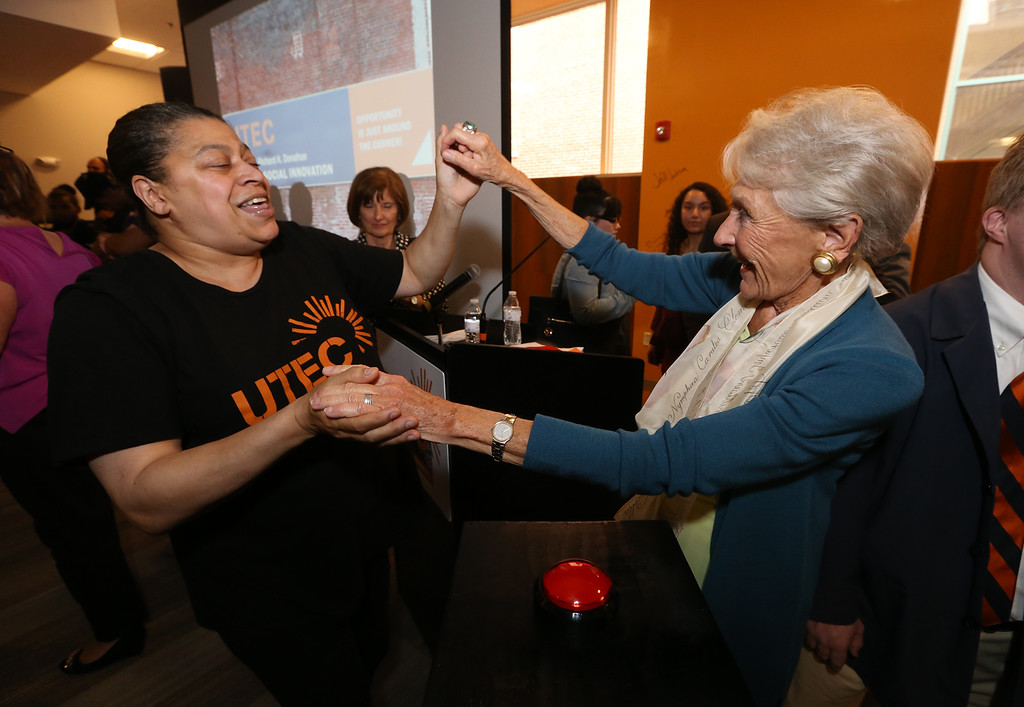 . Ribbon cutting and dedication of the Nancy L. and Richard K. Donahue UTEC Hub for Social Innovation. Nancy Donahue, right, dances with Joy Robinson of Lowell. (SUN/Julia Malakie)