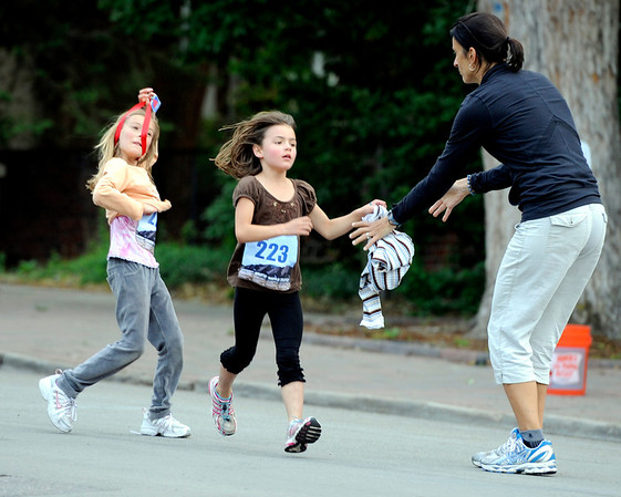 "Emma Perschke, 8, at left, and Sophie Spalding shed a layer of clothing and give it to Spalding's mother Laura during the family and friends division race on Thursday, June 9, during the Uni-Hill 2K run in the University Hill area of Boulder. For more photos and video of the race go to  <a href=""http://www.dailycamera.com"">http://www.dailycamera.com</a><br /> Jeremy Papasso/ Camera"