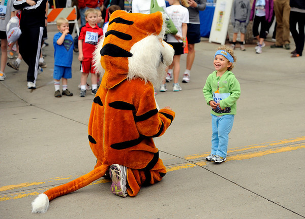 "Evan Henderson, 2, of Boulder, smiles as she is greeted by Sam Simeon, 17, of Erie, dressed as the Erie High School mascot on Thursday, June 9, during the Uni-Hill 2K run in the University Hill area of Boulder. For more photos and video of the race go to  <a href=""http://www.dailycamera.com"">http://www.dailycamera.com</a><br /> Jeremy Papasso/ Camera"