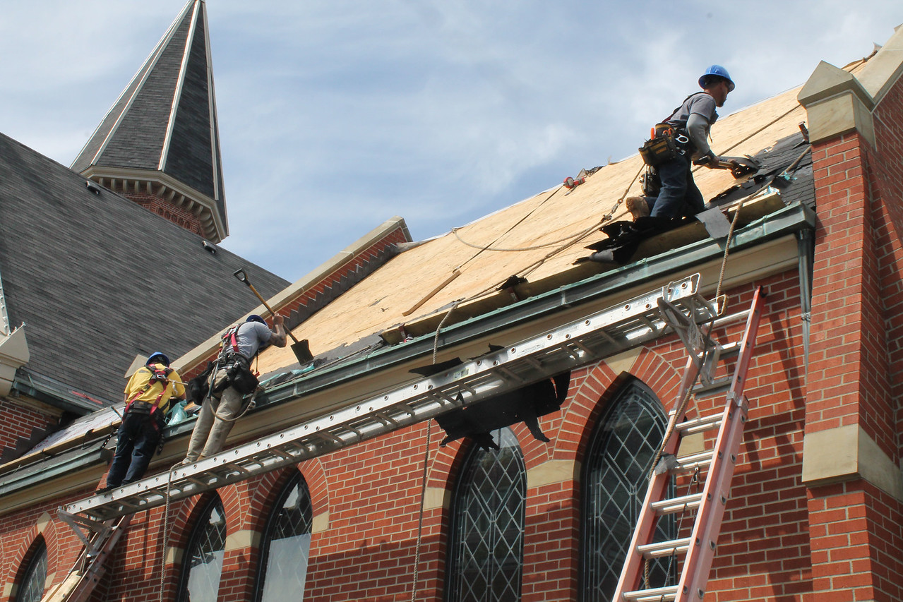 """LAWRENCE PANTAGES / GAZETTE Workers from Chippewa Roofing began tearing shingles off the United Church of Christ facility on Wednesday. The work is part of a $1.6 million renovation project that retiring Pastor Neal Sadler said is designed to make the facility last """"for the next 100 years."""""""