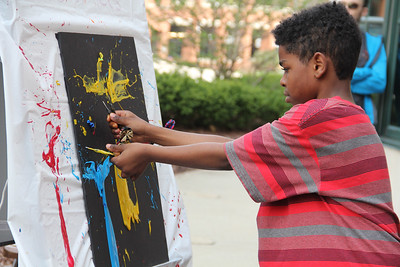 "ALEC SMITH / GAZETTE Deshaun Berry, 10, of Medina, pulls his paint-covered darts out of a work of art created Saturday at the Medina County District Library's Medina branch. Teen librarian Sean Rapacki called the event ""water balloon splatter."""