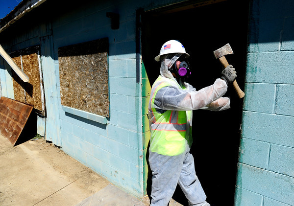 """Jaimie Garcia works to remove a door on one of the buildings on the site of an old mine as part of the Valmont Butte Remediation Project on Thursday May 10, 2012. <br /> Photo by Paul Aiken / The Boulder Daily Camera<br /> For a video of the project go to  <a href=""""http://www.dailycamera.com"""">http://www.dailycamera.com</a>"""