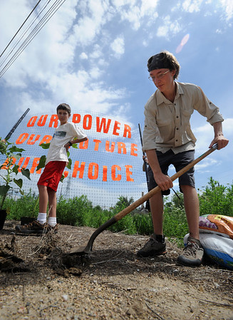 """Alex Budd gets the soil ready to plant sunflowers near the entrance of the Valmont Power Station.<br /> About 150 people rode bikes from the Central Park bandshell to the Valmont Coal Plant to protest its continued opening. The group  then planted sunflowers near the entrance on Saturday. For more a video and photos  of the protest, go to  <a href=""""http://www.dailycamera.com"""">http://www.dailycamera.com</a>.<br /> Cliff Grassmick / July 16, 2011"""