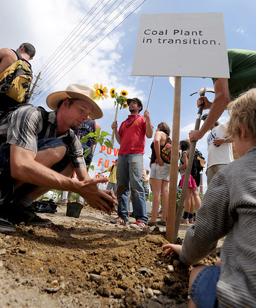 "Casey Coughlin, left, and his son, Teague, put up a sign at the planting site.<br /> About 150 people rode bikes from the Central Park bandshell to the Valmont Coal Plant to protest its continued opening. The group  then planted sunflowers near the entrance on Saturday. For more a video and photos  of the protest, go to  <a href=""http://www.dailycamera.com"">http://www.dailycamera.com</a>.<br /> Cliff Grassmick / July 16, 2011"