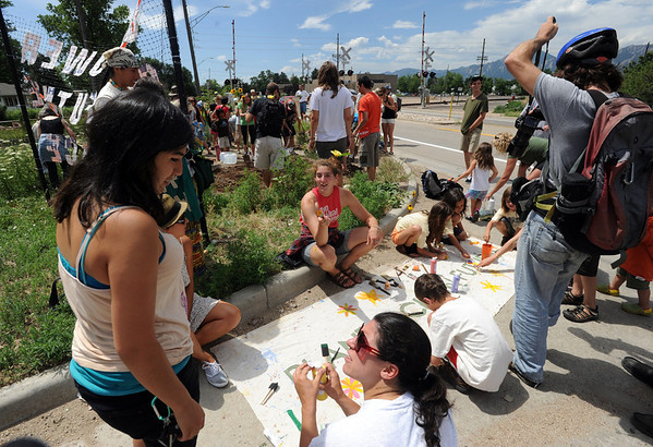 "The group paints a poster at the planting site.<br /> About 150 people rode bikes from the Central Park bandshell to the Valmont Coal Plant to protest its continued opening. The group  then planted sunflowers near the entrance on Saturday. For more a video and photos  of the protest, go to  <a href=""http://www.dailycamera.com"">http://www.dailycamera.com</a>.<br /> Cliff Grassmick / July 16, 2011"