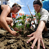 "Ayries Blanck, left, and Alex Budd, plant a sunflower in the ground at the entrance of the power plant.<br /> About 150 people rode bikes from the Central Park bandshell to the Valmont Coal Plant to protest its continued opening. The group  then planted sunflowers near the entrance on Saturday. For more a video and photos  of the protest, go to  <a href=""http://www.dailycamera.com"">http://www.dailycamera.com</a>.<br /> Cliff Grassmick / July 16, 2011"
