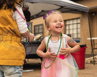 Two-year-old Emma Dike looks on with a smile as she dances to music during Vandi Gras, a Mardi Gras celebration for Van Zandt County, Saturday, Feb. 29, 2020, in Van.