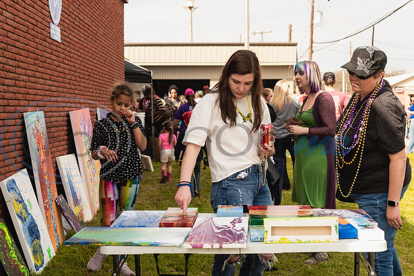 Community members check out local artists' paintings on display during Vandi Gras, a Mardi Gras celebration for Van Zandt County, Saturday, Feb. 29, 2020, in Van.