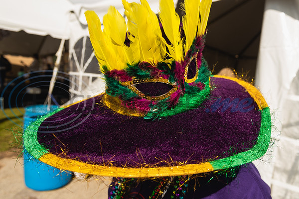 Allison Young dons a purple hat decorated with yellow feathers and a mask during Vandi Gras, a Mardi Gras celebration for Van Zandt County, Saturday, Feb. 29, 2020, in Van.