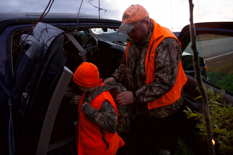 ELODIE REED - FOR THE BENNINGTON BANNER Rob Hamilton helps his grandson, Carson, 9, put on his backpack before the pair set out to go deer hunting in Bennington on Sunday for the second and last day of Youth Deer Weekend.