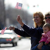 Shonda Holliman (left), Jo Fuller (center) and McKayla Holliman (right), 11 months old, wave flags during the Veteran's Day Parade on Main Street in Longmont, Colorado November 11, 2009. CAMERA/Mark Leffingwell