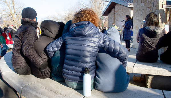 The sun was shining, but the wind was chilly. This family huddled together to keep warm during the vigil.