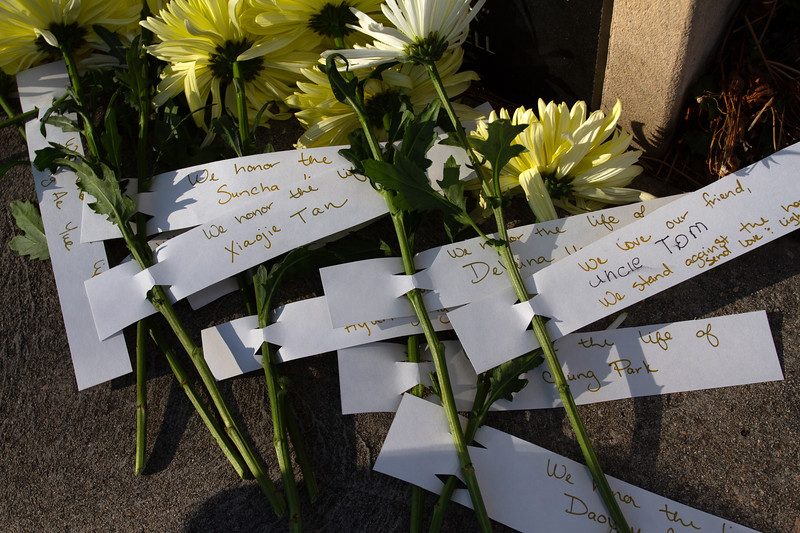Flowers that were left for the vigil with the names of victims attached.