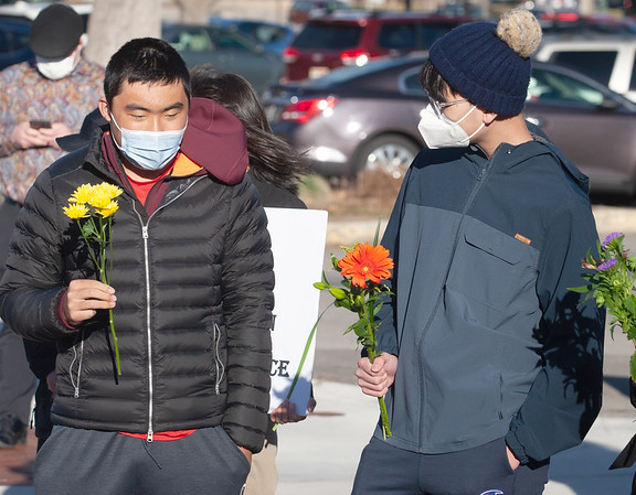 Jiang Huang and William Wang holding flowers for the Vigil for Asian American Hate Crime Victims at the Anne Frank Memorial.
