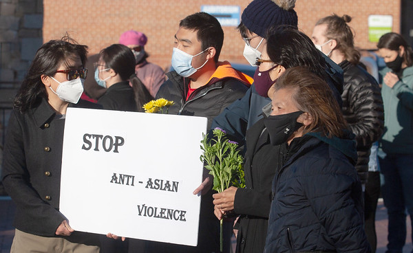 A group of Asian Americans hold up a sign during the Vigil for Asian American Hate Crime Victims at the Anne Frank Memorial.