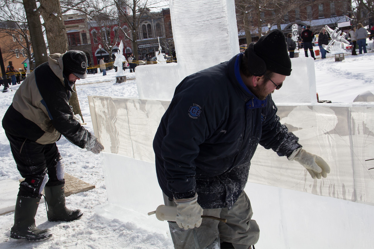 ALEC SMITH / GAZETTE George Niemoeller from Barberton (left) and Greg Demaline from Eastlake add finishing touches to an ice sculpture display depicting planets on Sunday during the 22nd Medina Ice Festival on Public Square. The pair were from Elegant Ice Creations of Broadview Heights.