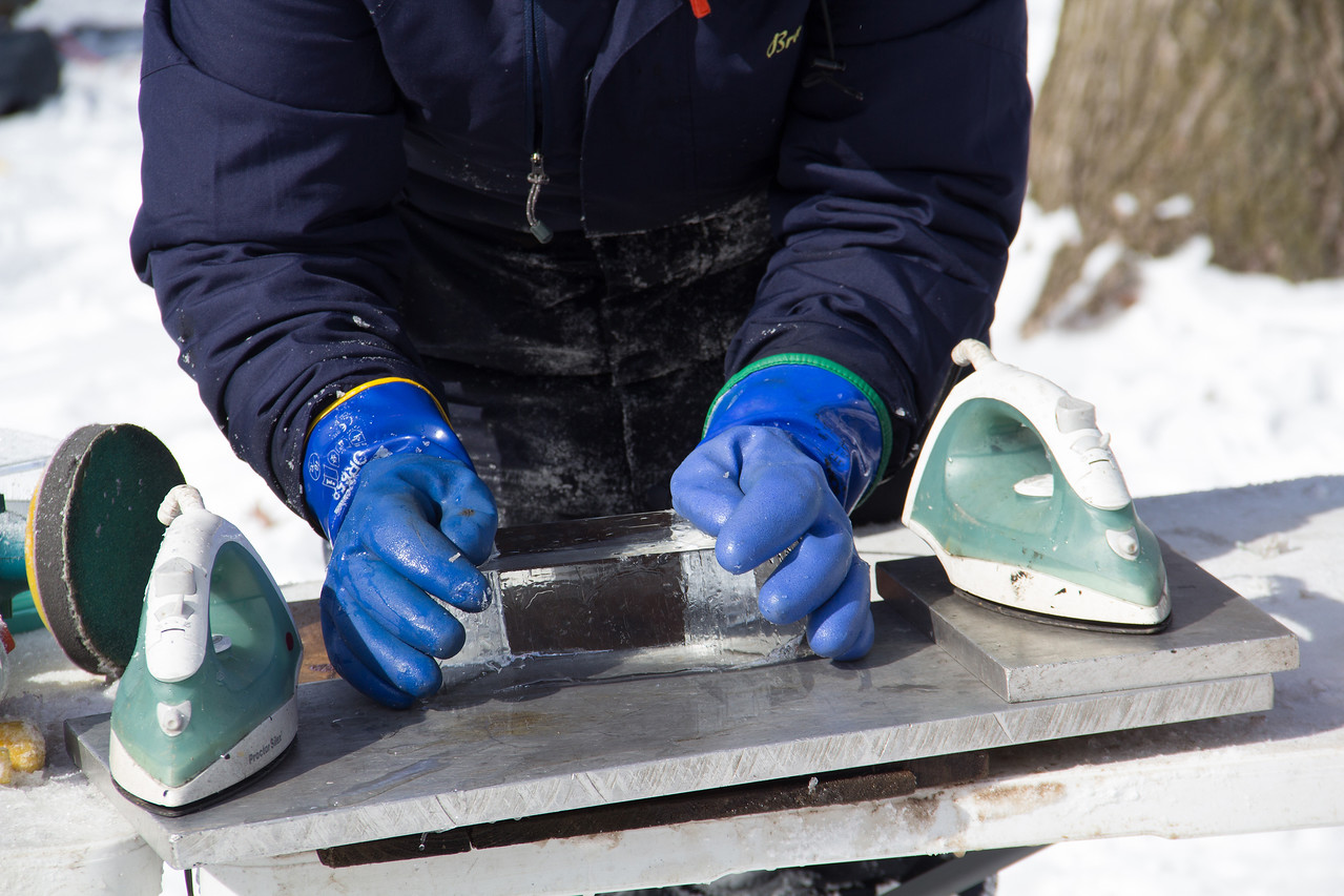 ALEC SMITH / GAZETTE Brandon Hartel of Akron uses heat to mold pieces of ice together on Sunday during the 22nd Ice Festival held on Medina's Public Square.