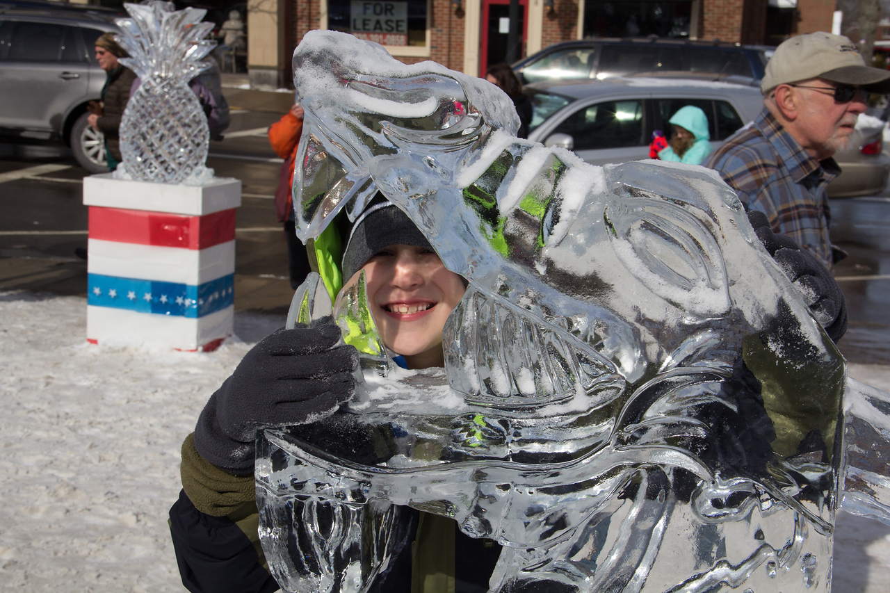 ALEC SMITH / GAZETTE Sam D'Attoma, 7, of Akron, enjoys getting up close with a dragon ice sculpture Sunday during the last day of the 22nd Medina Ice Festival.