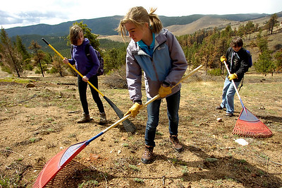 From left to right, Tobiah Nagle, Sydney Kinsey, Christian DeSouza students of the Watershed School, rake areas to be reseeded, on a 3 day project by the school to reseed areas of the Fourmile Fire burn area in the Sugarloaf Mountain Area. For more photos and a video of the project go to www.dailycamera.com Photo by Paul Aiken / The Camera / April 19, 2011