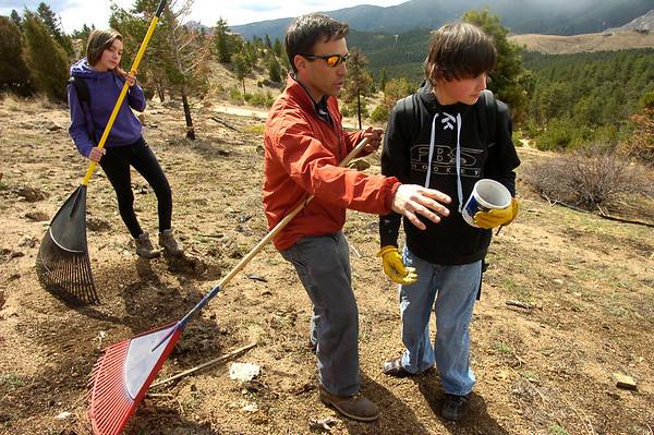 "Jason Berv, center, Head of School, instructs Christian DeSouza, right on seeding techniques as students of the Watershed School work on a 3 day project by the school to reseed areas of the Four Mile Fire burn area in the Sugarloaf Mountain Area. For more photos and a video of the project go to  <a href=""http://www.dailycamera.com"">http://www.dailycamera.com</a> Tobiah Nagle rakes the burned hillside in the background. <br /> Photo by Paul Aiken / The Camera / April 19, 2011"