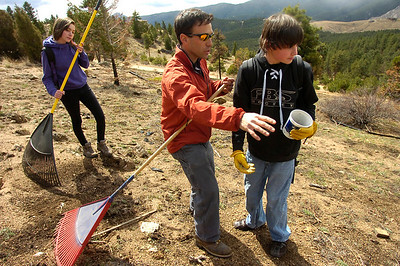 Jason Berv, center, Head of School, instructs Christian DeSouza, right on seeding techniques as students of the Watershed School work on a 3 day project by the school to reseed areas of the Four Mile Fire burn area in the Sugarloaf Mountain Area. For more photos and a video of the project go to www.dailycamera.com Tobiah Nagle rakes the burned hillside in the background.  Photo by Paul Aiken / The Camera / April 19, 2011