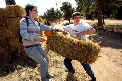 Ada Kakatsakis, left, and Soren Peterson, students at the Watershed School, carries straw bales to be placed on top of reseeded areas as part of  a 3 day project by the school to reseed areas of the Fourmile Fire burn area in the Sugarloaf Mountain Area. For more photos and a video of the project go to www.dailycamera.com Photo by Paul Aiken / The Camera / April 19, 2011