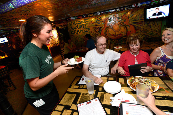 "Kelly Hughes, a linguistics and communications Senior at the University of Colorado delivers and order of nachos to the table including from left to right Dennis and Pat Schwarzentraub and their daughter-in-law Kimberly Schwarzentraub during the lunch rush at the Sink on University Hill in Boulder on Monday afternoon July 16, 2012. Hughes works 30 plus hours a week while taking a full load of classes. <br /> For more photos and a video of the working college students go to  <a href=""http://www.dailycamera.com"">http://www.dailycamera.com</a><br /> Photo by Paul Aiken"