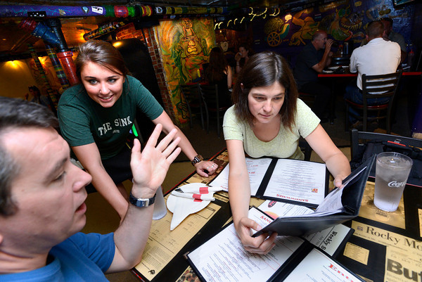 "Kelly Hughes a Linguistics and Communications Senior at the University of Colorado discusses the menu with Jean Francois Doussin, left and Agnes Borbon, during the lunch rush at the Sink on University Hill in Boulder on Monday afternoon July 16, 2012. Hughes works 30 plus hours a week while taking a full load of classes. For more photos and a video of the working college students go to  <a href=""http://www.dailycamera.com"">http://www.dailycamera.com</a><br /> Photo by Paul Aiken"