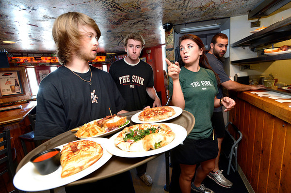 """Kelly Hughes, a Linguistics and Communications Senior at the University of Colorado gives food delivery instructions to fellow student  Evan Almon, at left during the lunch rush at the Sink on University Hill in Boulder on Monday afternoon July 16, 2012. Both Hughes and Almon work at the restaurant while taking a full load of classes. Trainee Bernie Conley, center, looks on.For more photos and a video of the working college students go to  <a href=""""http://www.dailycamera.com"""">http://www.dailycamera.com</a><br /> Photo by Paul Aiken"""