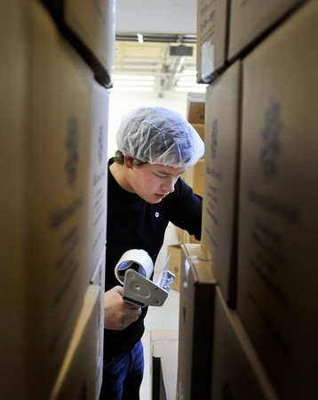 20120225_KENYA_505.jpg Alec Gee, 16, of Longmont, tapes a box of packaged meals shut as they are prepared to be shipped to Kenya during the Kids Around the World Kare for Kenya project in Gunbarrel on Saturday, February 25, 2012.<br /> <br /> (Greg Lindstrom/Times-Call)