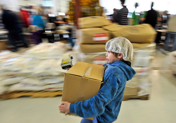 20120225_KENYA_449.jpg Jerry Martinez, 11, of Broomfield, moves a box full of packaged meals, ready to be shipped to Kenya, during the Kids Around the World Kare for Kenya project in Gunbarrel on Saturday, February 25, 2012.  Each box contains 36 packages and feeds 216 children, according to the Kids Around the World program.<br /> <br /> (Greg Lindstrom/Times-Call)