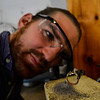 KRISTOPHER RADDER — BRATTLEBORO REFORMER<br /> Will Nevins-Alderfer, co-owner of W.R. Metalarts, looks at the placement of the diamond setting on the ring before soldering them together.