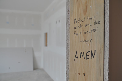 "ASHLEY FOX / GAZETTE Church members went through writing prayers and Bible passages on wall studs at the new Radiant Life structure. Here, a member wrote a blessing in what will be one of two rooms for infants at the school portion of the ""community center."""