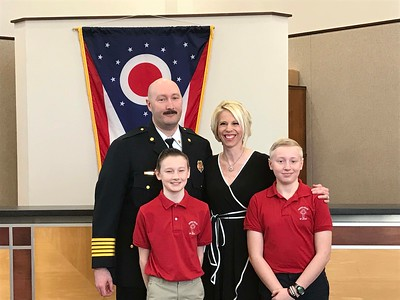 NATHAN HAVENNER/ GAZETTE  Newly sworn in Wadsworth Fire Chief Robert Lindner is pictured in council chambers with wife Andrea, and sons Carson, left, and Grant, 13, right, Monday.