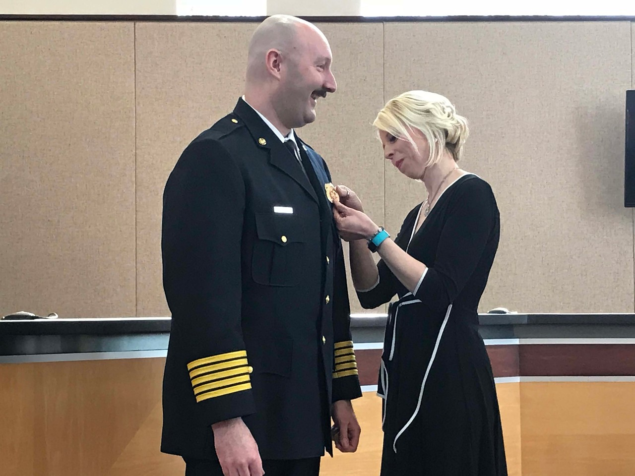 NATHAN HAVENNER/ GAZETTE  Andrea Lindner performs the pinning ceremony for her husband Robert following his swearing in as fire chief by Mayor Robin Laubaugh at city hall, 120 Maple St. Monday morning.