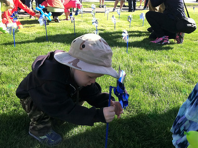 "BOB SANDRICK / GAZETTE Henry Heisler, 2, plants a pinwheel in the ""garden"" in front of St. Francis Xavier Church at the Pinwheel Walk sponsored by the Children's Center of Medina County."