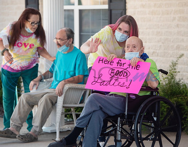 Residents and staff of Wateron at Shiloh, a healthcare, rehabilitation and assisted living center, wave as decorated cars parade around their building in Tyler on Thursday, May 7, 2020. Families of residents were encouraged to join the parade to celebrate the upcoming Mother's Day holiday as visitors are not allowed inside their facilities at this time due to COVID-19 precautions.
